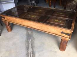 Coffee table made from hand painted door (Antique). Glass table top.