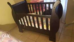 Solid wooden cot with a Safeway car seat