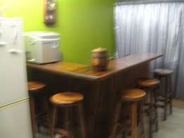 An L shaped Bar counter with 6 solid teak stools
