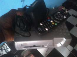 Dstv decoder with remote and smart card.