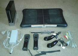 Nintendo Wii console, sensor bar, Wii Fit Board with two remotes and t