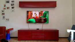 Red Ikea TV cabinet with floating shelf