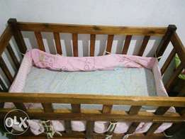 Baby cot with mattress and mattress cover.