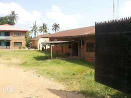 2 and half acres of land with buildings on it by d road side at Apata