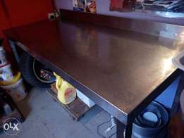 Stainless steel commercial kitchen table and assorted baking tins