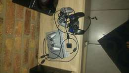 Silver Sony Playstation 2 with 3 remotes,12 games and memory card