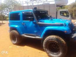 owner selling a blue shinny jeep