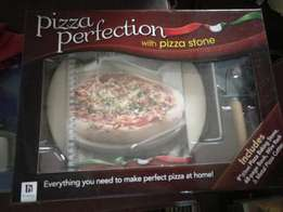 Pizza perfecting with pizza stone. Pizza set.