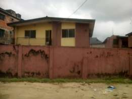 A story building 2bedroom flat on half plot at ikosi ketu with C of O