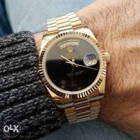 Gold Rolex watch with black dial