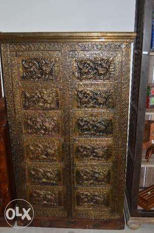 a solid wood cupboard with full copper doors