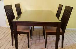 Dining room table with glass top and 4 chairs.