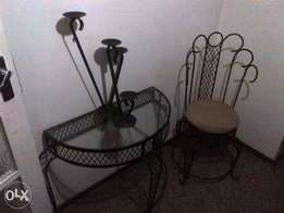 Cast iron table,chair and candle stick holders.