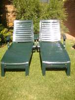 Two poolside plastic loungers