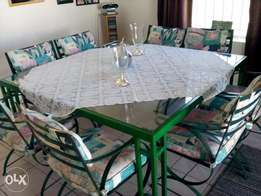 Patio dining table & 8 chairs in solid steel with glass top.