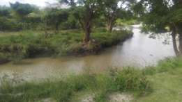 25 acres agricultural land touching athi river already registered .