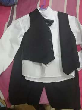 Black boys suit, with white shirt, bow tie and waist coat.