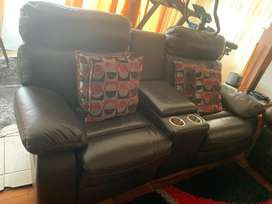 Two seater genuine leather couche with console.