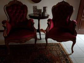 Antique Red Velvet Wingback Chairs with carved wood detailing.