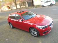 Image of BMW 118i, 2015 model, Red in color, Automatic with a sunroof for sale