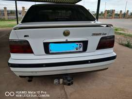 White BMW 318is, 1998 model with taw bar and reverse parking sensors.
