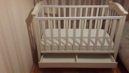 Детская кроватка с ящиком для белья, одежды или игрушек.