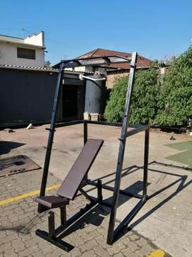 Squat rack with pull up bar and adjustable bench.