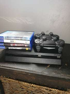 1TB Playstation 4 with 2 remotes and 4 games
