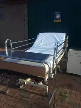 Hospital bed with mattress and steel side table and serving trolley