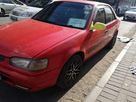 A red Toyota corolla for urgent sale.