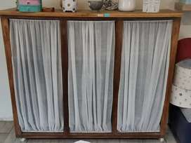 Wooden cupboard with curtain closure