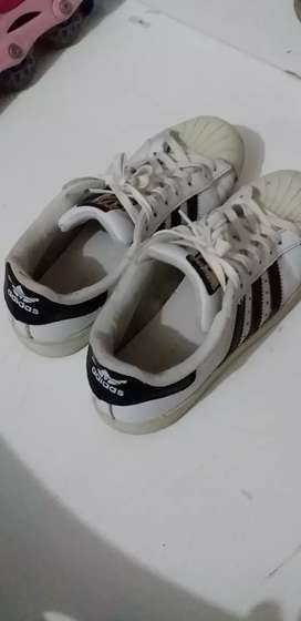 White Adidas Superstar shoe .